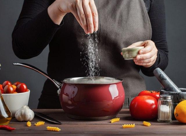 hands adding salt to pasta water