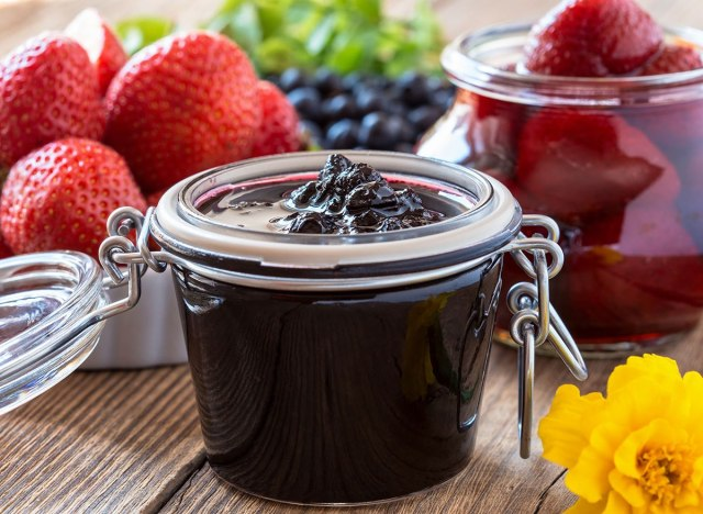 jar of blueberry jam compote with fresh strawberries