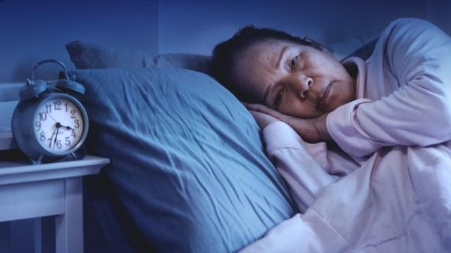 senior woman having sleep disorder, sitting in bed look sad