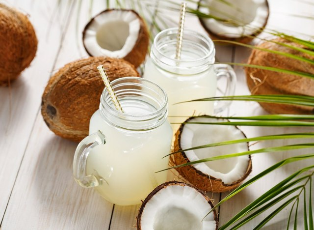 maron jar mugs filled with coconut water around coconuts